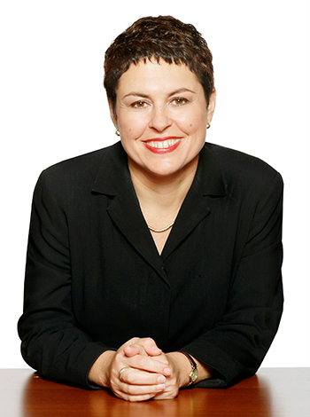 Lynne Kosky the former education minister is smiling into the camera and sitting down leaning on a desk
