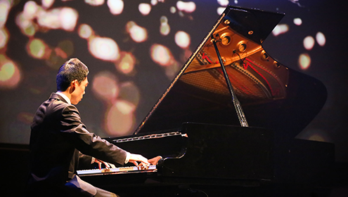 A man plays a piano on a darkened theatre stage, with a speckled visual backdrop