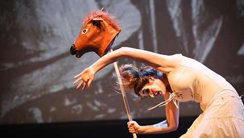 A woman wearing a white dress and white makeup holds a horse head prop with her arms in the air against a grey backdrop