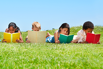 a group of young children lying on the field reading books