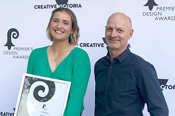 a young woman holding a certificate and a man standing next to her in front of a creative victoria banner