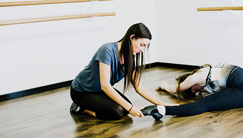 A female VET Dance student helping another student doing leg stretches