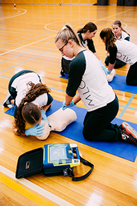 Students performing a CPR on a dummy