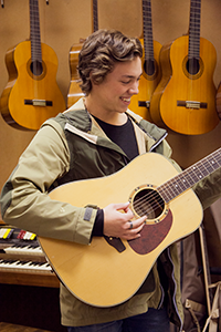 A male student playing a guitar as part of his VET Music Industry program